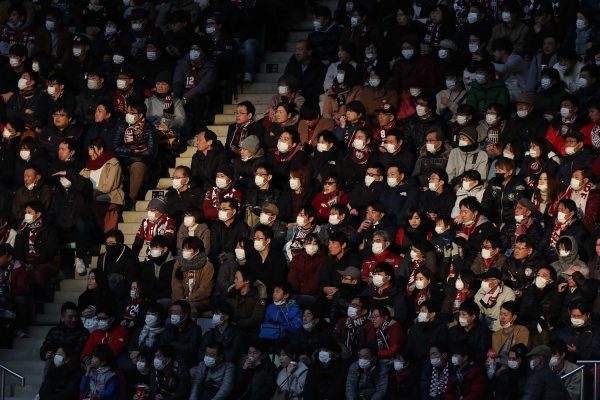 TOPSHOT - This picture taken on February 23, 2020 shows audience members wearing face masks at a J.League football match between Vissel Kobe and Yokohama F. Marinos in Kobe. - The Japanese government has urged people to avoid large gatherings, and Tokyo's government has cancelled some large public events over COVID-19 coronavirus fears that has now killed more than 2,400 people and spread around the world. (Photo by STR / JIJI PRESS / AFP) / Japan OUT (Photo by STR/JIJI PRESS/AFP via Getty Images)