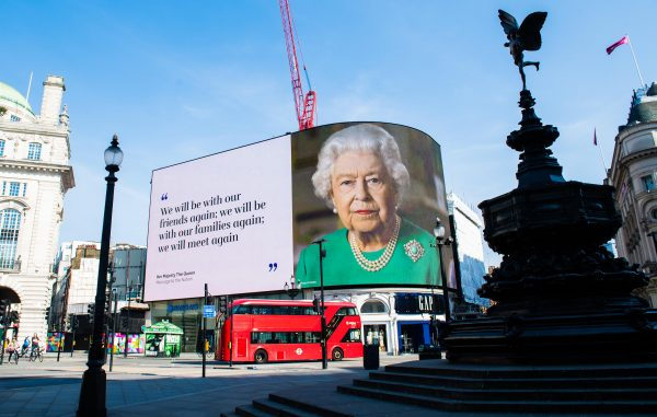 LONDON, ENGLAND - APRIL 10: An image of Queen Elizabeth II and quotes from her broadcast to the nation in relation to the coronavirus epidemic are displayed on screens in Piccadilly Circus on April 10, 2020 in London, England. (Photo by Samir Hussein/WireImage)